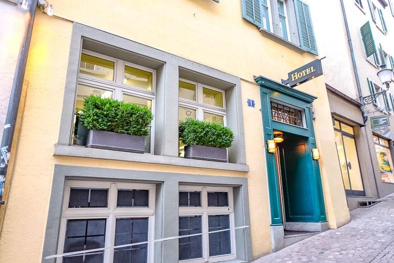 Gelbes Hotel mit grüner Tür an Kopfsteinpflasterstraße in Züricher Altstadt