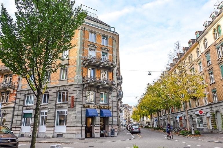 Oranges Hotel aus Stein an Straßenecke mit Straße gesäumt von Bäumen im Hintergrund