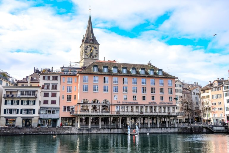pink hotel on waterfront with clocktower behind where to stay in zurich