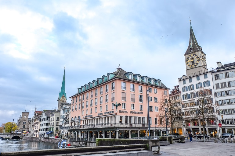 pink hotel at waterfront with two church towers behind zurich where to stay lindenhof
