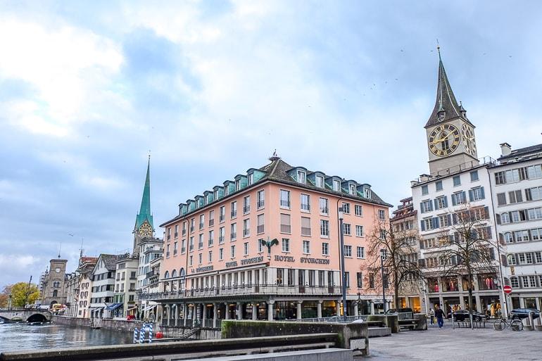Pinkes Hotel an Wasserufer mit zwei Kirchtürmen im Hintergrund Wo übernachten in Zürich