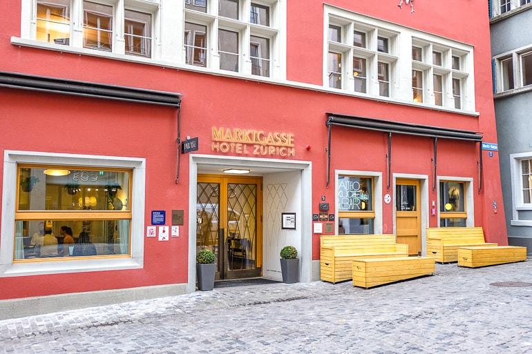 Rotes Hotel mit Holzbänken und Kopfsteinpflasterstraße im Vordergrund in Zürich Altstadt
