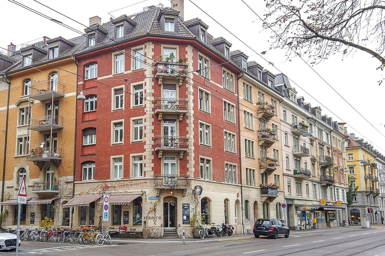 red guesthouse on street corner on zurich