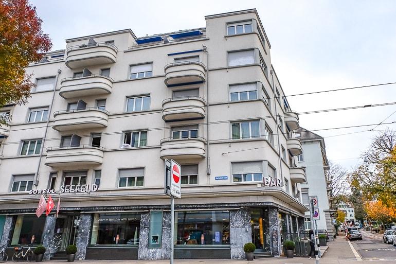 Weißes Hotel mit Balkonen mit Blick auf die Straße an Straßenecke