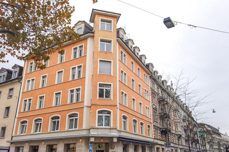 Oranges Hotel mit Fenstern an Straßenecke und Bäumen in der Nähe