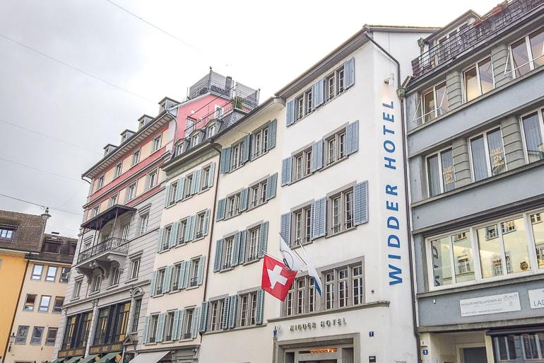 Weißes Hotel mit wehenden roten Schweizer Flaggen