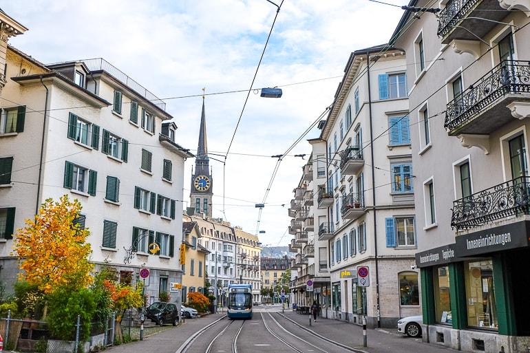 Geschäftige Straße mit Läden und Straßenbahn und Kirchturm im Hintergrund