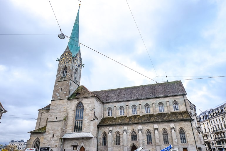church with pointy green clock tower and clouds behind in zurich