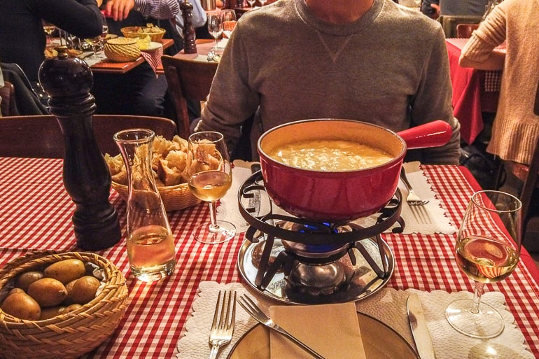 red fondue pot on table with wine and food baskets in zurich switzerland