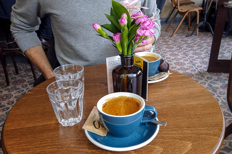 coffees in blue mugs on wooden cafe table with flowers