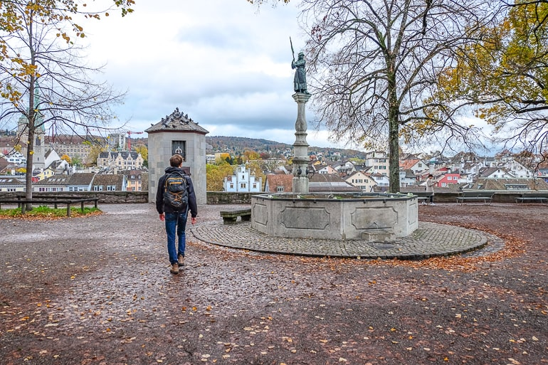 man walking through park with fountain lindenhof hill zurich