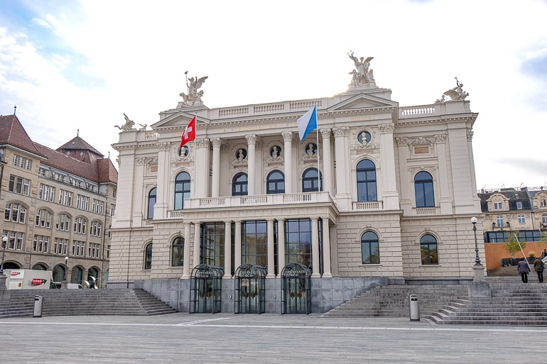 grand opera house with flags and open square in front in zurich