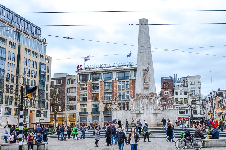 hotel with flags in city square behind monument where to stay in amsterdam