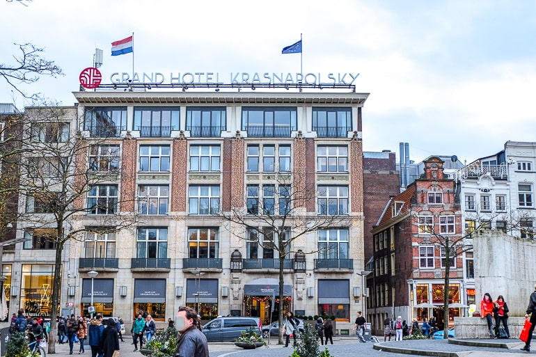 hotel with windows and flags overlooking city square amsterdam