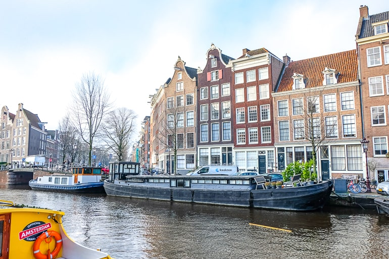 black houseboat floating in canal with houses behind in amsterdam