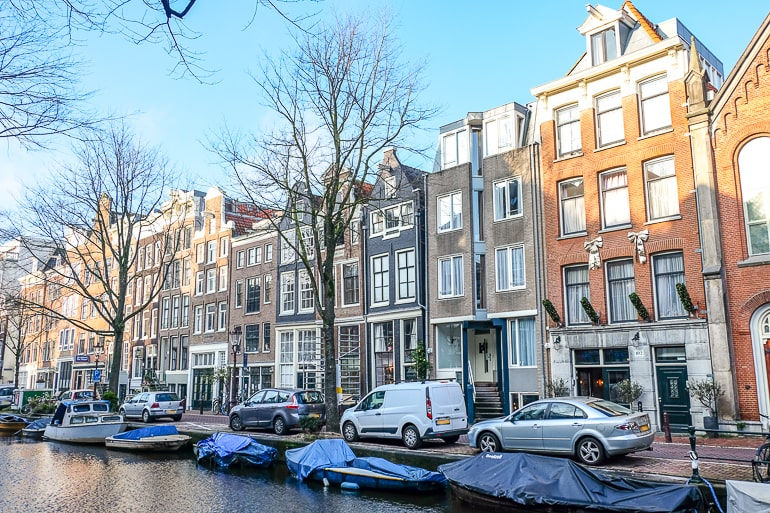 colourful houses with windows and cars parked in front in amsterdam