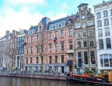 red hotel in tall houses with canal in front where to stay in amsterdam