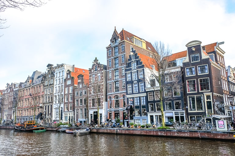 colourful tall skinny buildings in amsterdam neighbourhood canal belt