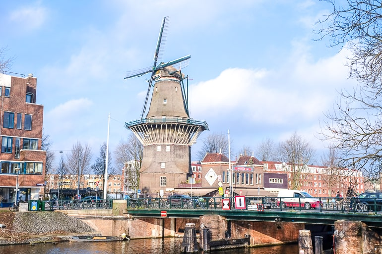 tall windmill with blue sky behind and river in front in zeeburg amsterdam