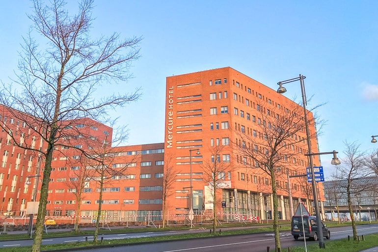 orange brick hotel with trees in front in amsterdam