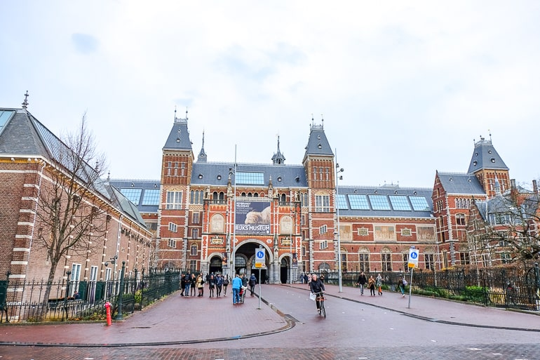 red brick museum with people walking on street in amsterdam where to stay