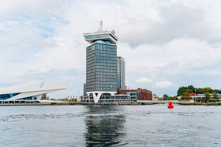 tall glass tower standing by river edge in amsterdam
