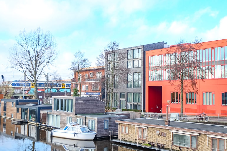 apartment buildings with river and houseboats in front in zeeburg amsterdam