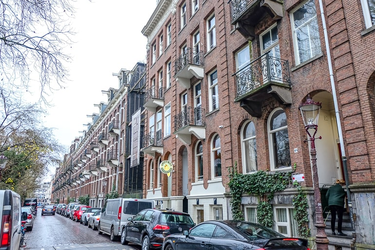 red brick houses in a row with cars parked on street in amsterdam