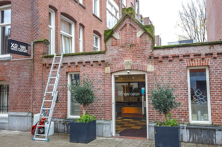 small brick hotel entrance with ladder in front in museum quarter amsterdam
