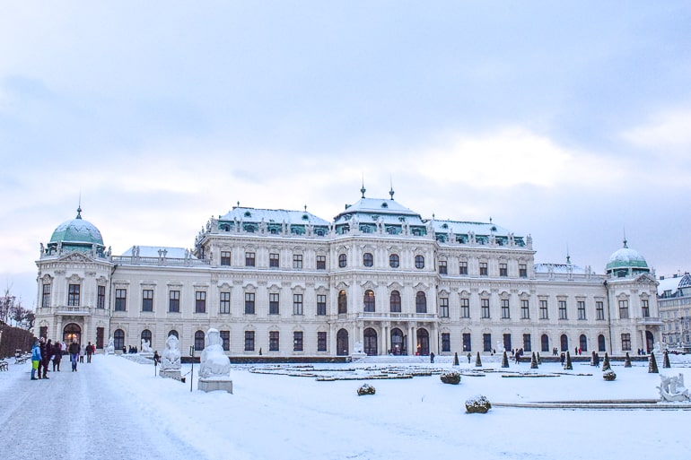 large palace building with snowy gardens in front in vienna