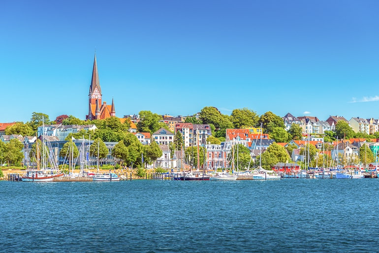 church up on hill with houses below and shoreline in front flensburg germany