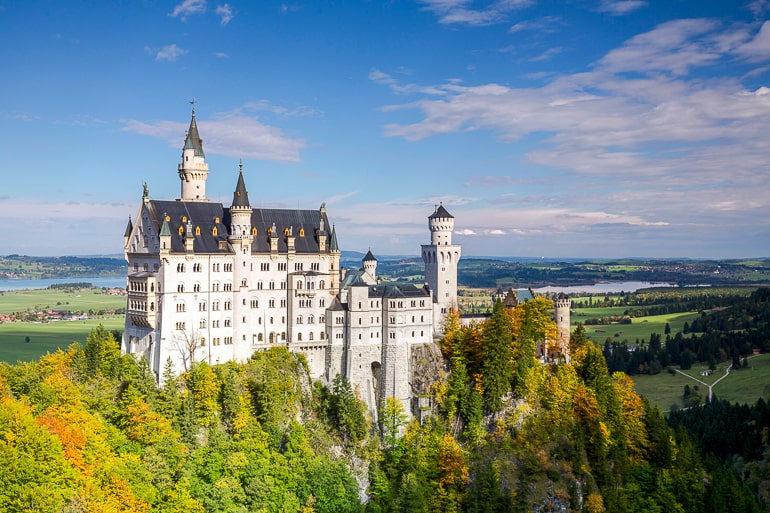 white medieval castle on hilltop with blue sky and countryside behind in germany
