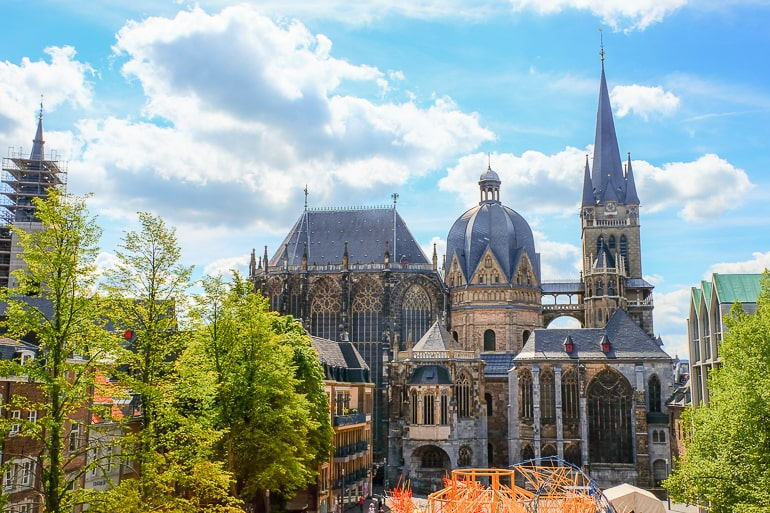 large cathedral with tower and dome in aachen with blue sky behind