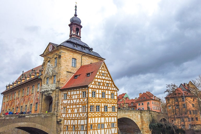 yellow old town hall building with bridges over river in bamberg germany
