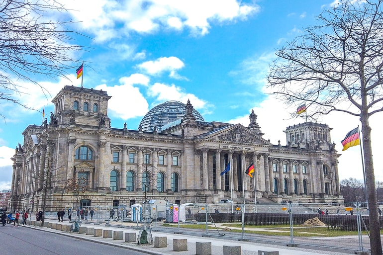 domed building with german flags flying in berlin on germany itinerary