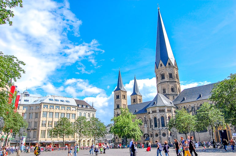 tall church spire and open public square with blue sky above in bonn germany