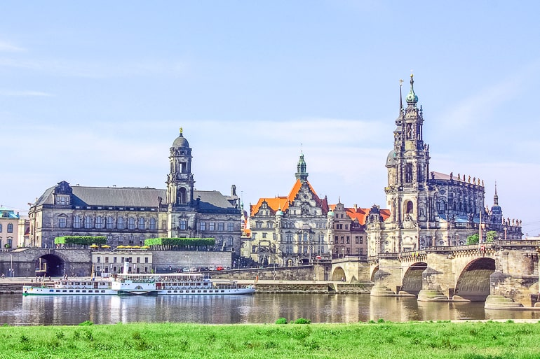 tall church towers with old bridge crossing river in dresden germany itinerary