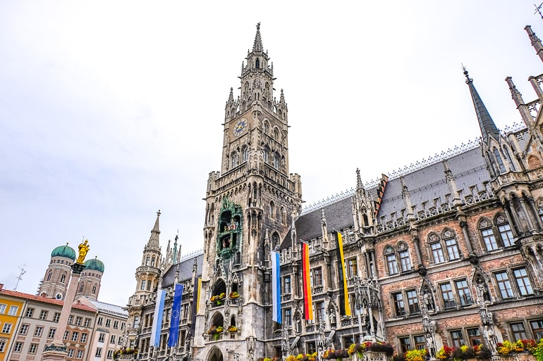 tall tower with flags of new town hall in munich germany itinerary