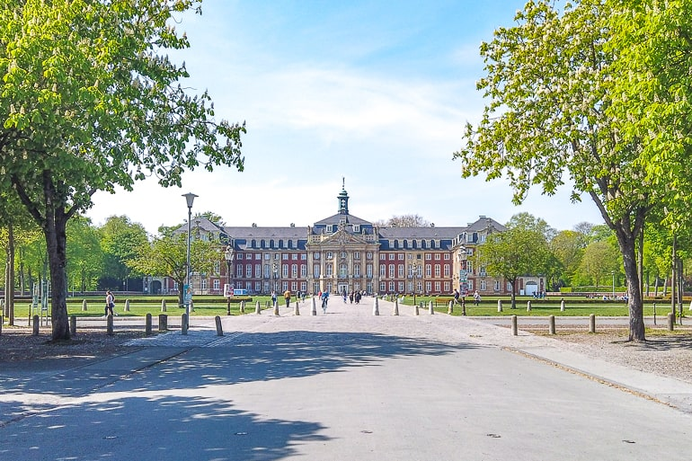 large palace building with laneway and trees beside in munster germany