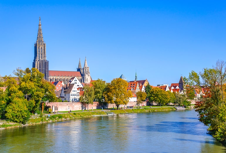 tall church tower among old town building by rivers edge in ulm germany