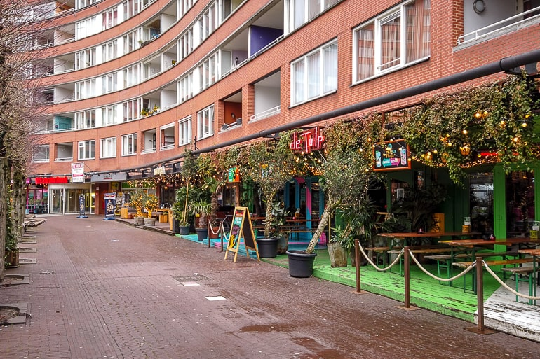 red brick building with restaurant patios on the ground level in amsterdam