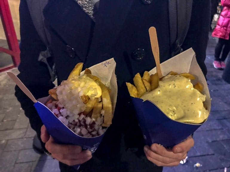 two helpings of fries held by man at night one day in amsterdam