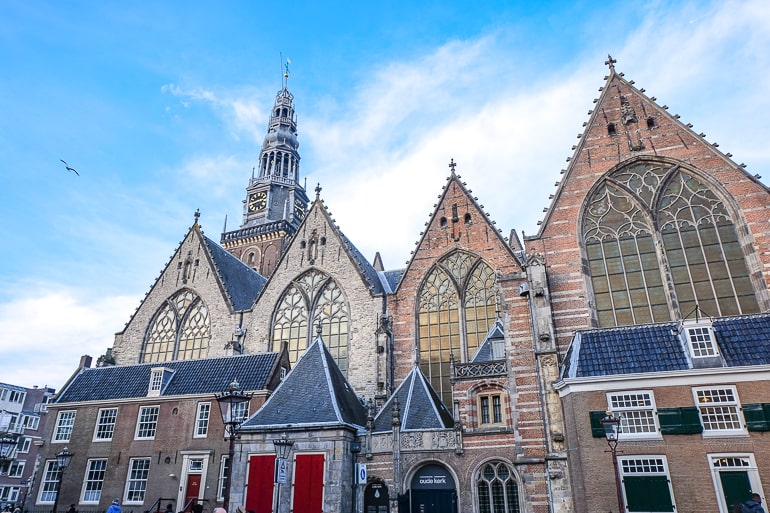 old church with clock tower and glass windows in old town amsterdam