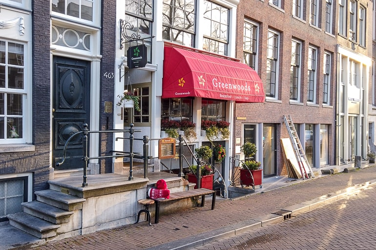 red awning over breakfast place entrance one day in amsterdam