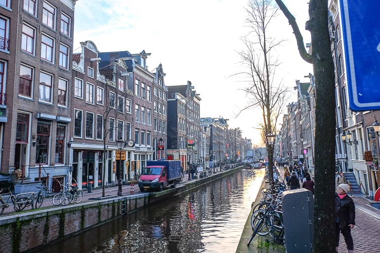 city canal in red light district with setting sun one day in amsterdam