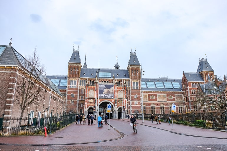 large red brick museum with wide lane in front in amsterdam rijksmuseum