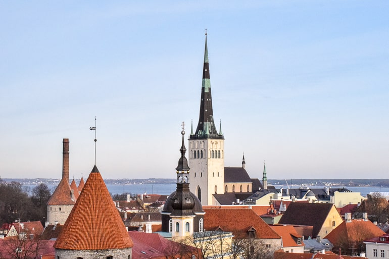 green and white church tower above old town roofs in tallinn estonia one day itinerary