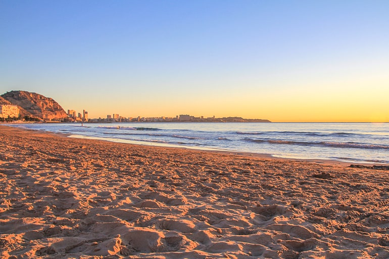 sandy beach with hill in distance at sunset in alicante spain