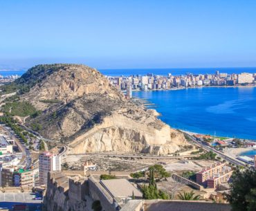 view of rocky cliff with blue water and beach beside things to do in alicante spain