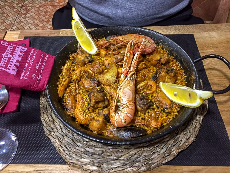dish of paella on table with prawn and lemons alicante spain